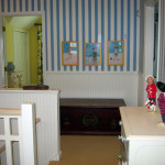 After: We put up wainscoting and a nautical blue and white striped wall paper to bring the guest wing hall to life.